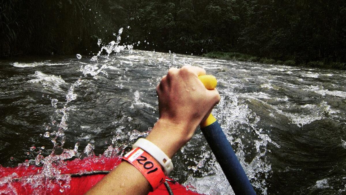 Imagem da visão de alguém descendo o rio, com a mão segurando um remo e descendo o rio