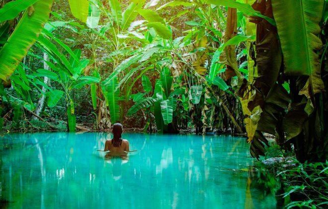 Mulher dentro de um lago com a água super clara no Jalapão, com várias bananeiras em volta.